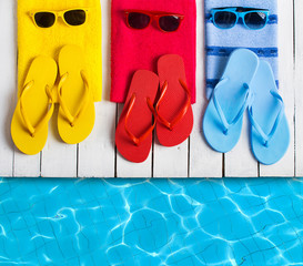Flip flop shoes and sunglasses of young people near hotel pool