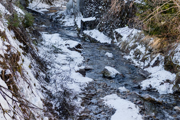 mountain stream in the middle of snow and rocks along banks of r