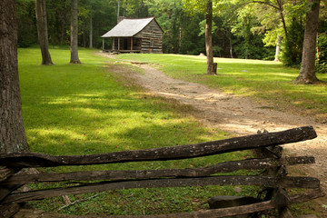 Old log farmhouse with a dirt path and fence