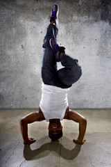 Inverted black breakdancer doing a handstand or urban yoga
