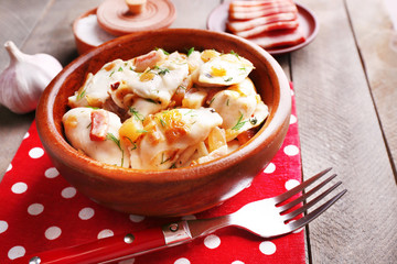 Fried dumplings with onion and bacon in frying pan,