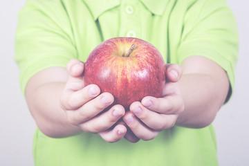 manos de niño con una manzana