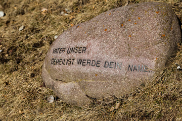 German sentence from The Lord's Prayer printed on a rock on wi