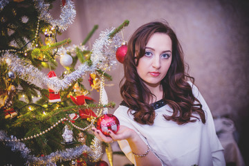 Beautiful young woman stands against christmas tree