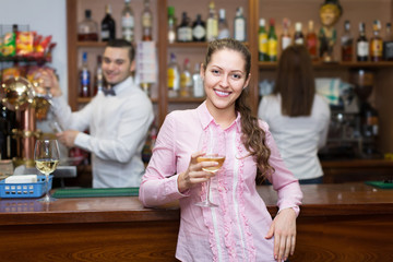 Girl standing at bar with glass of wine.