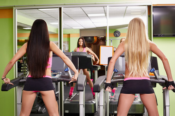 Rear view of sporty girls exercising on treadmills