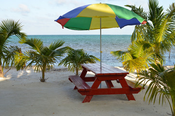 Table with umbrella on the beach of Caye Caulker