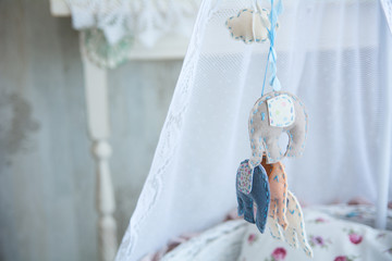 Closeup of soft toys hanging on a cot
