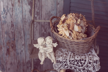 Two plaster angels in the arms sitting on a bench on a vintage b