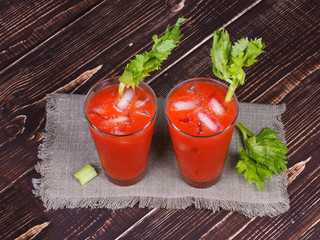 Bloody mary cocktails served with celery on wooden background