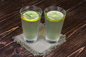 Lemonade with fresh lemon and tarragon on wooden background