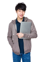 Young asian man holding laptop computer