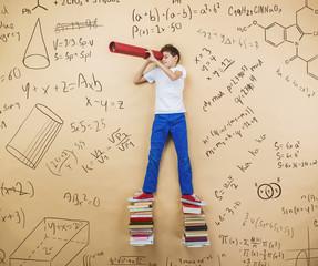 Cute little boy learning playfully in frot of a big blackboard