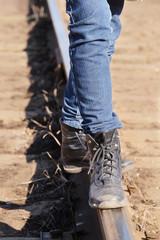Girl legs on the railway tracks