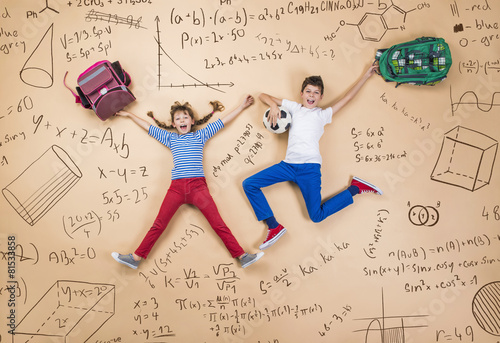 Leinwanddruck Bild Cute boy and girl learning playfully in frot of a big blackboard