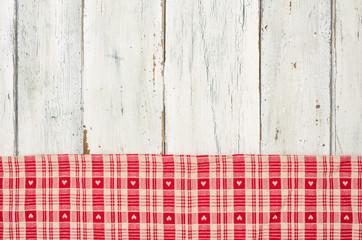 Rot kariertes Tischtuch mit Herzen vor weißem Holzhintergrund