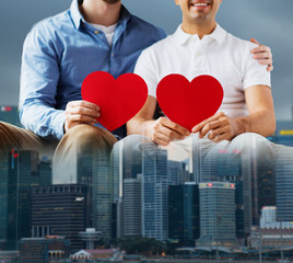 close up of happy gay male couple with red hearts