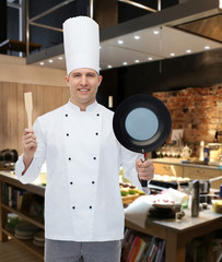 happy male chef holding frying pan and spatula