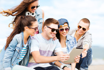group of teenagers looking at tablet pc