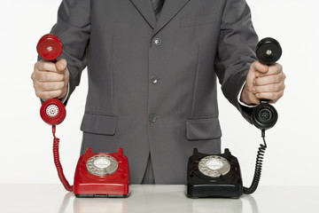 businessman offering assistance with two different telephone