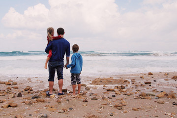father, son and daughter walking on the beach