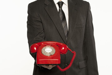 businessman offering assistance holding a red vintage telephone