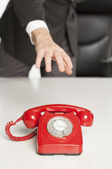 Businessman reaching for a red phone