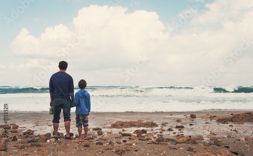 father and son walking on the beach - 81535211