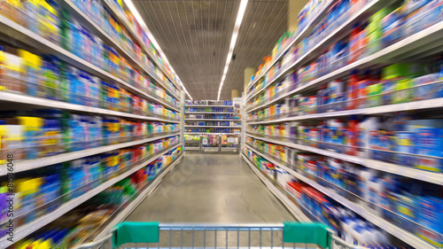 Leinwanddruck Bild Shopping Cart View on a Supermarket Aisle and Shelves - Image Ha