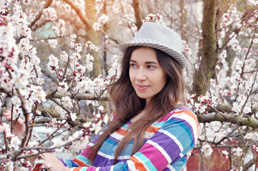 Beautiful woman in a hat in the blossoming spring garden