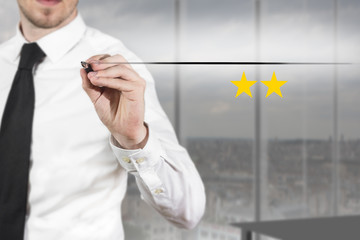 businessman in office writing two golden stars