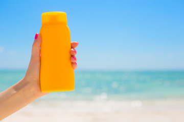 Woman holding sunscreen bottle in hand on the beach