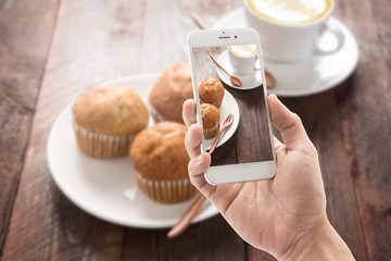 Taking photo of muffin and coffee on wooden table