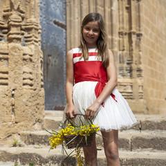 Niña con vestido de fiesta rojo y blanco y cesta con flores