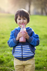 Cute boy, drinking healthy strawberry smoothie in the park