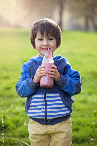 Cute boy, drinking healthy strawberry smoothie in the park - 81537822