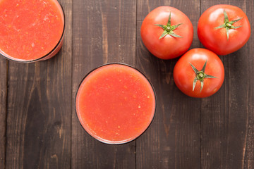 Top shot vegetable smoothie made of red ripe tomatoes on wooden