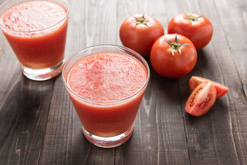 Healthy vegetable smoothie made of red ripe tomatoes on wooden t