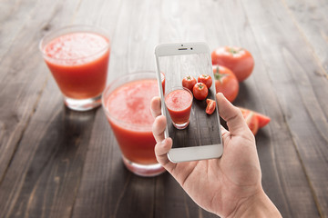 Taking photo of vegetable smoothie made of red ripe tomatoes on