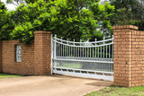 White wrought iron driveway entrance gates in brick fence