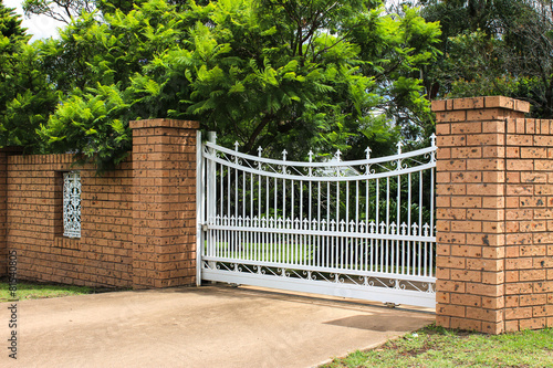 Leinwanddruck Bild White wrought iron driveway entrance gates in brick fence