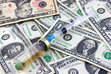 syringe for injection, an ampoule with medication and dollars
