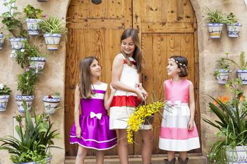 Niñas con vestidos de fiesta y ramo de flores