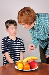 Strict woman showing a cute young boy fruit he has to eat