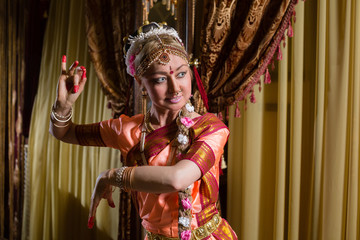 White woman is dancing in traditional indian dress