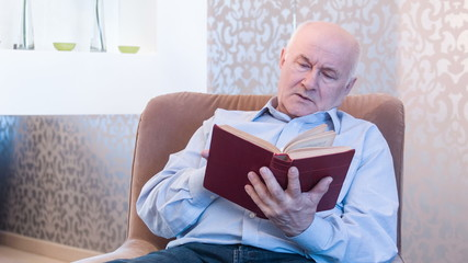 Retired man reading interesting story