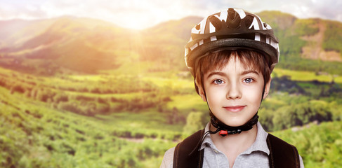 smiling boy cyclist over mountains background collage