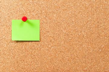 Single sticky note green on cork board horizontal