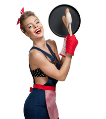 Attractive housewife wearing apron with kitchen utensils