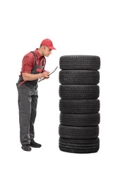 Young mechanic checking quality of tires